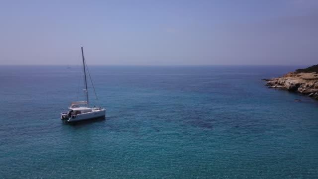 sailboat anchored in remote cove, group sunbathes on beach - 40 49 lat filmów i materiałów b-roll