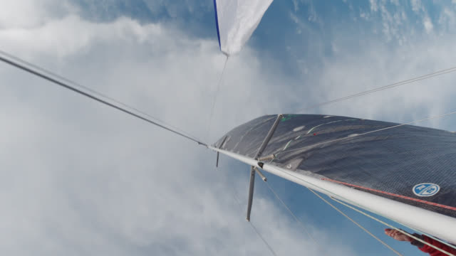 A Sailboat Captain in His Sixties Hoists the Jib on his Sailboat in Puget Sound in Washington on a Partly Cloudy Day