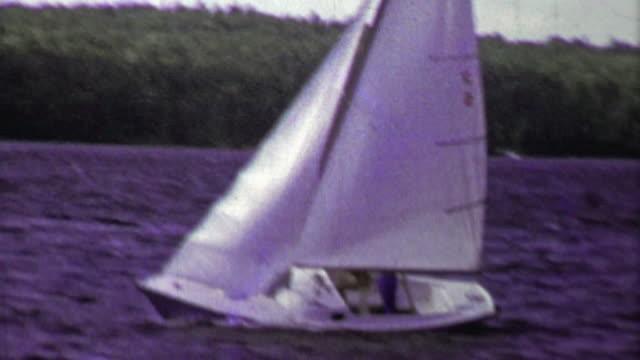 1961: Sailboat full speed ahead on choppy dark blue waters. video