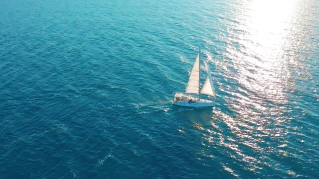Zeilboot in de Oceaan. Witte zeiljacht in het midden van de grenzeloze Oceaan. Luchtfoto video