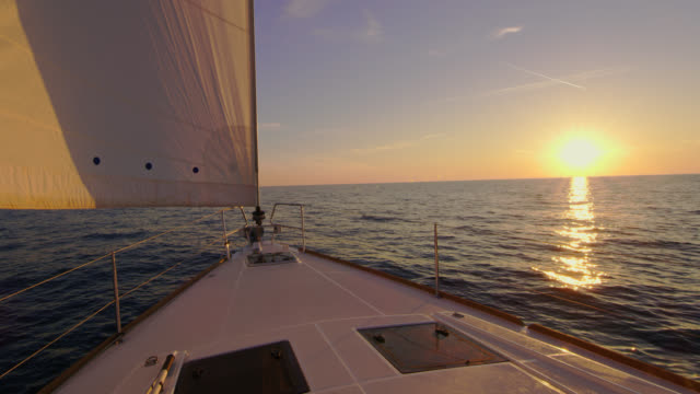 vídeos de stock e filmes b-roll de slo mo sailboat sailing at sunset - veleiro