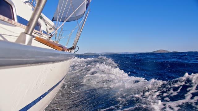 SLO MO Sailboat sailing the sea Slow motion shot of a sailboat sailing toward the coast. Side view of a body of the sailboat. Adriatic Sea. Croatia. recreational boat stock videos & royalty-free footage