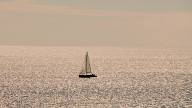 A sailboat, yacht on the horizon in sunset video