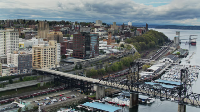 Sailboats and Freight trains on Downtown Tacoma Waterfront - Drone Shot