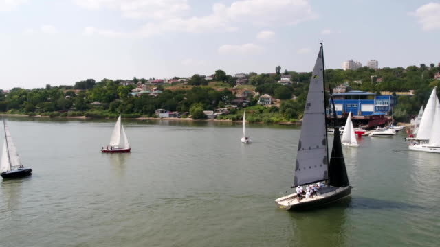 Sailboats floating on the lake. Footage. Competition sport of sailing. Yacht and beautiful seascape. Summer travel video