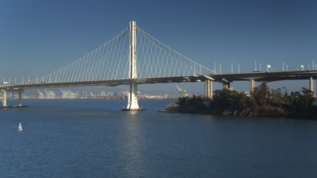 Sailboats Under the Bay Bridge - Drone Shot Aerial shot of the eastern section of the Bay Bridge, that spas San Francisco bay between Yerba Buena Island and Oakland. The Port of Oakland is visible in the distance. oakland stock videos & royalty-free footage