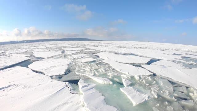kış aylarında dondurulmuş denizde yelkenli tekne. - donmuş su stok videoları ve detay görüntü çekimi