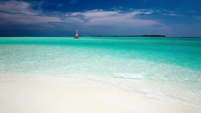 Sailing boat with red sail on a beach of deserted tropical island video