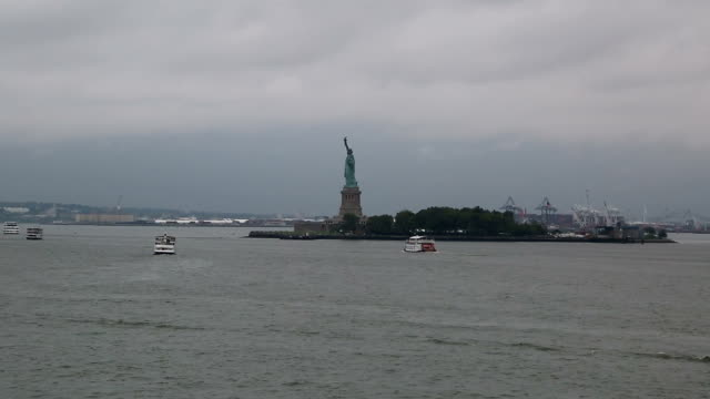 Sailing by The Statue Of Liberty on a gloomy day - New York City, United States