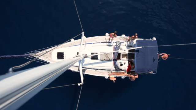 Sailing fun Group of friends jumps in the water from the boat. Shot from the top of the mast. yachting stock videos & royalty-free footage