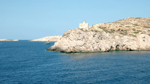 sailing past the lighthouse in ormos harbor on the island of ios, greece