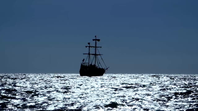Sailing ship silhouette on sunset background Sailing ship silhouette on sunset background. Lot of glares on sea surface. Black boat with two mast is floating away on the water. Sunny summer evening. Black sea coast. mast sailing stock videos & royalty-free footage