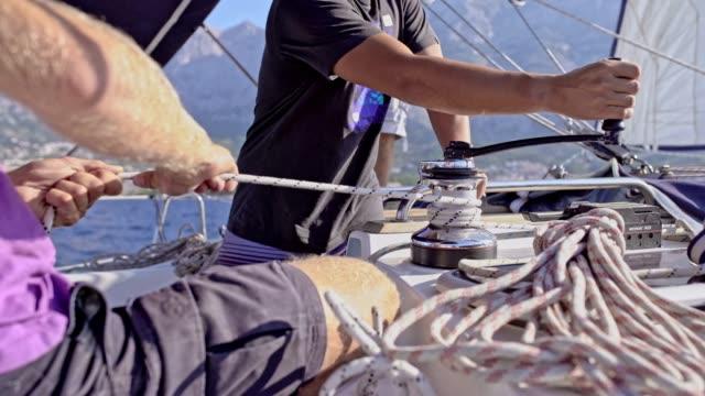 4K Sailing team adjusting crank and rigging on sunny sailboat, real time video
