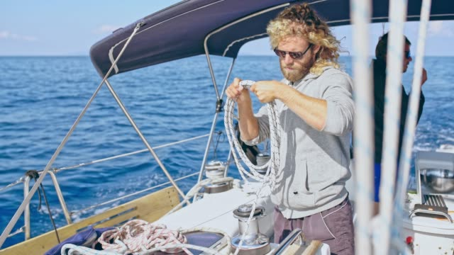 4K Sailing team adjusting rigging on sunny sailboat, real time 4K Sailing team adjusting rigging on sunny sailboat. MS, pan up, real time. mast sailing stock videos & royalty-free footage
