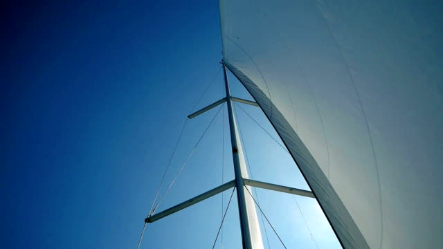 Sailing trip in Croatia Sailing boat main mast with perfectly curved main sail and blue sky behind. Filmed from boats cockpit in slow motion hd. mast sailing stock videos & royalty-free footage