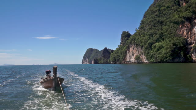 Sailing vacation fist person point of view The point of view scene from a boat on the Andaman Sea.  Enjoying the view towards Ko Talabeng, Krabi, Thailand.  A traditional wooden Longtail taxi boat being towed.  A perfect sailing vacation scene. towing stock videos & royalty-free footage