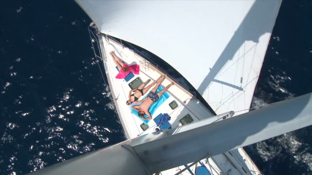HD: Sailing HD720p: Directly above view on a group of people sunbathing on the deck of a sailing boat. Slow-motion. sunbathing stock videos & royalty-free footage
