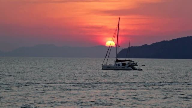 Sailing yacht illuminated by the light of the sun setting Sailing yacht illuminated by the light of the sun setting pattaya stock videos & royalty-free footage