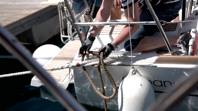 Sailor inties rope on handling appliance Sailor inties rope on handling appliance. Hands pulling ropes, winding sheets around winches close-up. Sailor's hand on a winch of sailing boat. Sailing. regatta stock videos & royalty-free footage