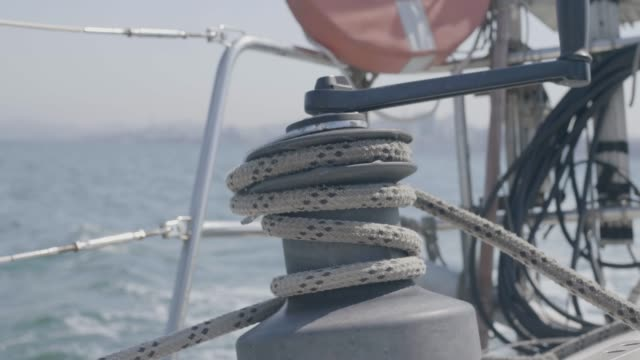 Sailor man using sail winch and rope while sailing on yacht in sea close up Sailor man using sail winch and rope while sailing on yacht in sea close up. Sailboat winch and rope yacht detail. Yachting in sea crank mechanism stock videos & royalty-free footage
