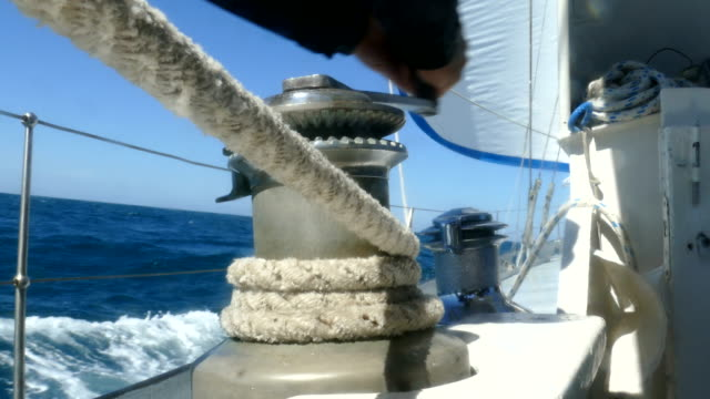 Sailor manages a sail on the winch Sailor manages a sail on the winch mast sailing stock videos & royalty-free footage