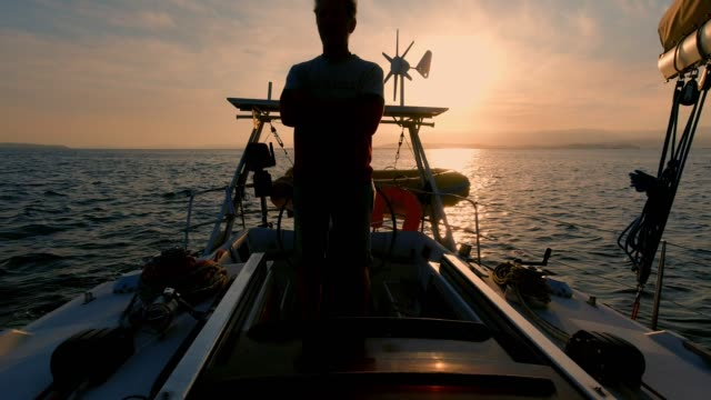 sailor on a sailboat at sunset, twilight time on the sea, backlight shooting, sea tour in the Atlantic ocean sailor on a sailboat at sunset, twilight time on the sea, backlight shooting, sea tour in the Atlantic ocean, 4k 25fps recreational boat stock videos & royalty-free footage