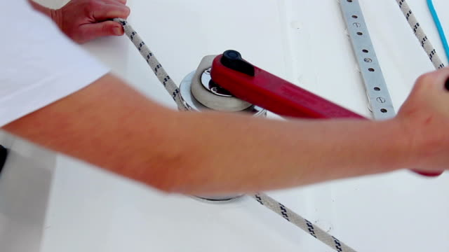 Sailor securing rope, mooring a sailboat, yachting, maintenance video