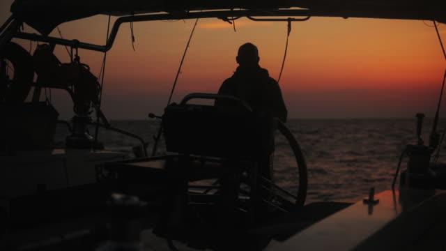 sailor using wheel to steer rudder on a sailing boat. - ster fragment pojazdu filmów i materiałów b-roll