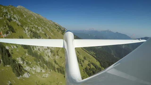LD Sailplane gliding along a green mountain in sunshine