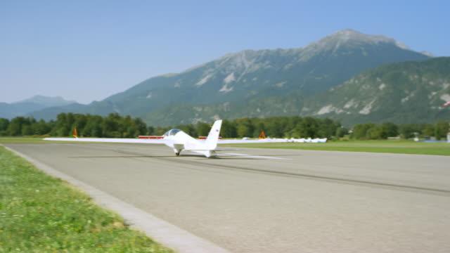 Sailplane landing on the sunny airstrip