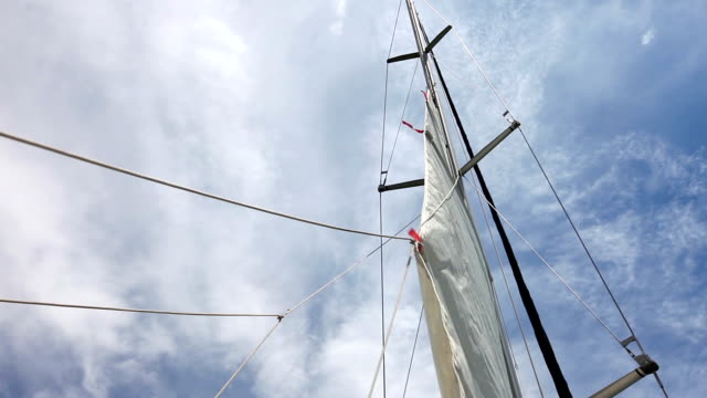 HD: Sails up, sailor is hoisting the mainsail video