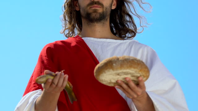 Saint Jesus Christ in robe stretching fish and bread into camera, son of God