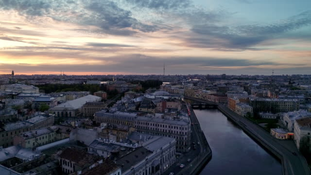 Saint Petersburg on a sunny spring morning. Colorful low-rise buildings on both banks of the river. A road bridge crosses a quiet river. treedeo saint petersburg stock videos & royalty-free footage