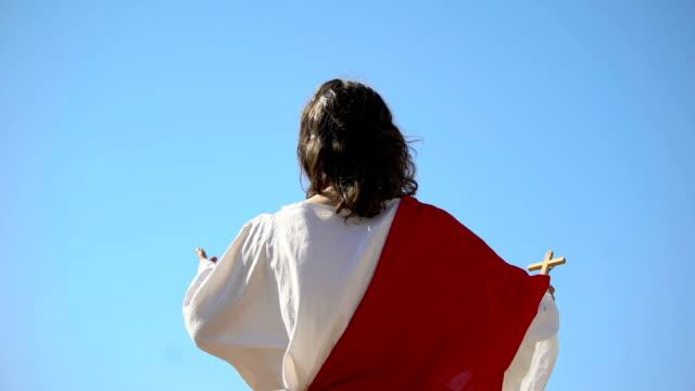 vidéos et rushes de saint prophète retenant la croix, priant à dieu, prêchant le christianisme vue arrière - baptême