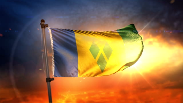 saint vincent and the grenadines flag backlit at beautiful sunrise loop slow motion 4k - kingstown video stock e b–roll