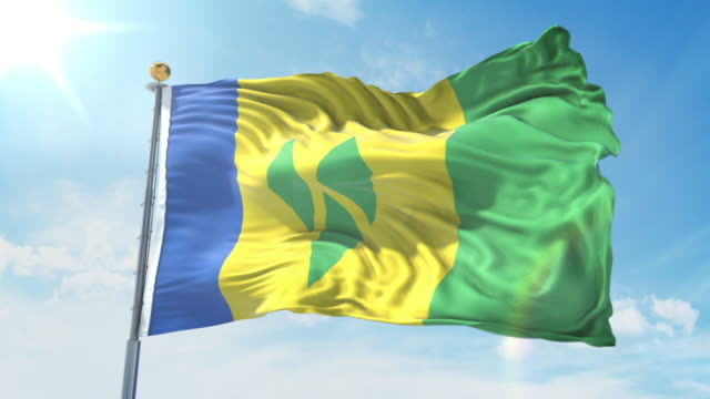 saint vincent and the grenadines flag waving in the wind against deep blue sky. national theme, international concept. 3d render seamless loop 4k - kingstown video stock e b–roll