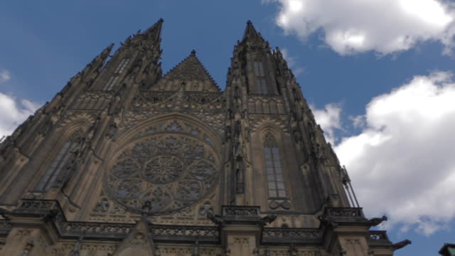 Saint Vitus cathedral in Prague. Pan to left in low angle with cloudy beautiful blue sky during the afternoon.