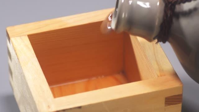 日本の四角い木のメジャーカップでお酒を - 習字点の映像素材/bロール