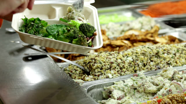 Salad bar customer fills to-go container. A woman serves herself at a healthy salad bar.  Container is made of bio-degradable plant-based materials and is suitable for composting. kitchen utensil stock videos & royalty-free footage