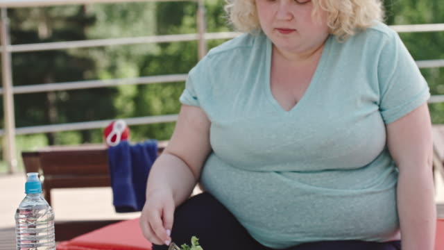 Salad Hater Tilt up of overweight blonde woman forcing herself to eat green salad on a diet fat nutrient stock videos & royalty-free footage