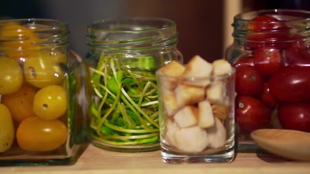 Ingredientes de ensalada de pan crujiente en frascos, tomates, verde vegetal - vídeo