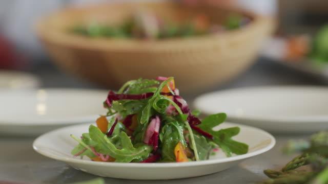 salad is placed on plate - mestiere nella ristorazione video stock e b–roll