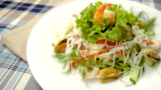 Salad with mussels, shrimps, squid, lettuce, tomatoes, cheese. Slow motion. HD