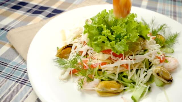 stockvideo's en b-roll-footage met salade met mosselen, garnalen, inktvis, sla, tomaten, kaas. slow motion. hd - venkel