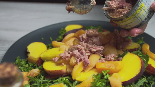 Salad with peaches and vegetables. Women's hands close up add tuna, meat to the salad