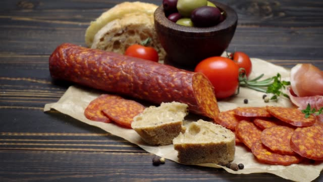 salami or chorizo sausage close up on a wood board video
