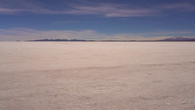 Salar de Uyuni salt flat with Ande mountains and sky Salar de Uyuni salt flat with Ande mountains and sky in Bolivia, South America salt flat stock videos & royalty-free footage