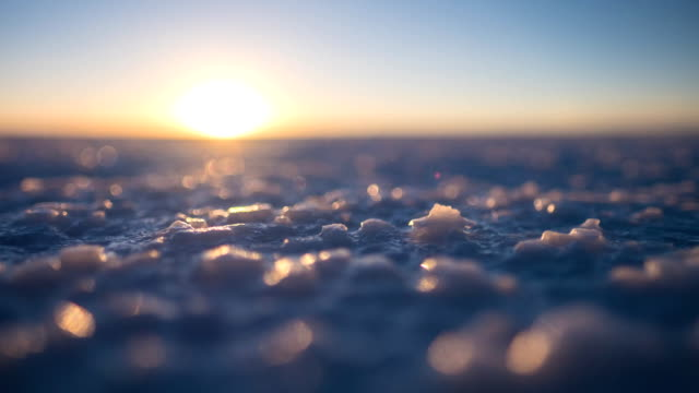 Salar de Uyuni Salar de Uyuni at sunset. Timalapse of the salt flat of Salar de Uyuni during sunset, Bolivia. Focus on the foreground, on the salt crystals. salt flat stock videos & royalty-free footage
