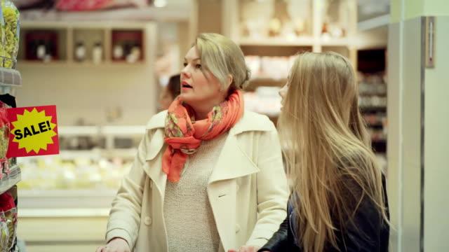 vídeos y material grabado en eventos de stock de venta en la tienda de comestibles. mujer con hija elige descuentos de productos - eventos de etiqueta