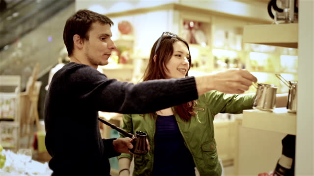 sale, consumerism and people concept shopping - happy young couple choosing cezve for Turkish coffee in mall video
